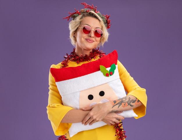 Erfreute junge blonde frau mit weihnachtskopfkranz und lametta-girlande um den hals, die ein weihnachtsmann-kissen hält, das isoliert auf lila wand mit kopierraum aussieht