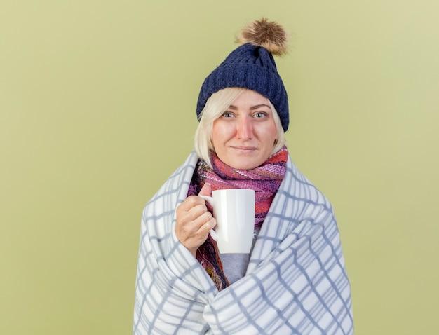 Erfreute junge blonde kranke slawische frau, die wintermütze trägt