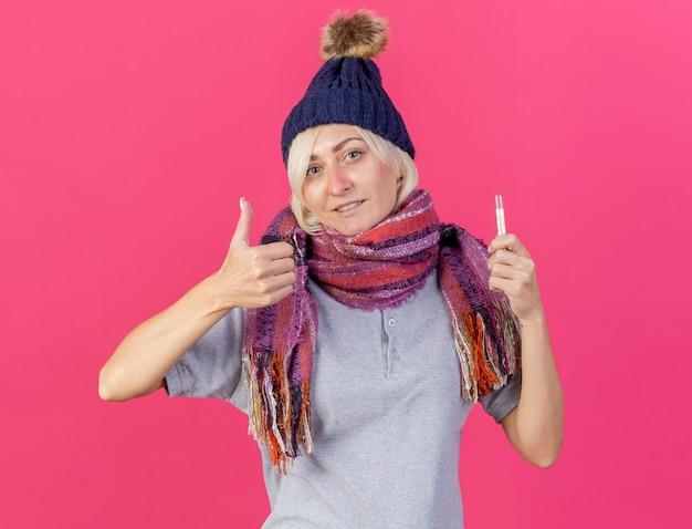 Erfreute junge blonde kranke slawische frau, die wintermütze und schal daumen hoch trägt