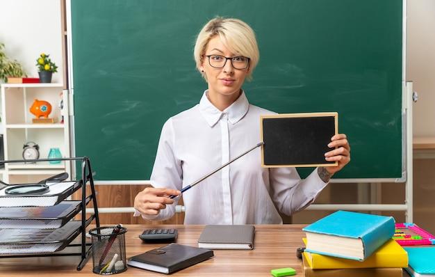Erfreute junge blonde lehrerin mit brille, die am schreibtisch mit schulwerkzeugen im klassenzimmer sitzt und eine mini-tafel zeigt, die mit einem zeiger darauf zeigt