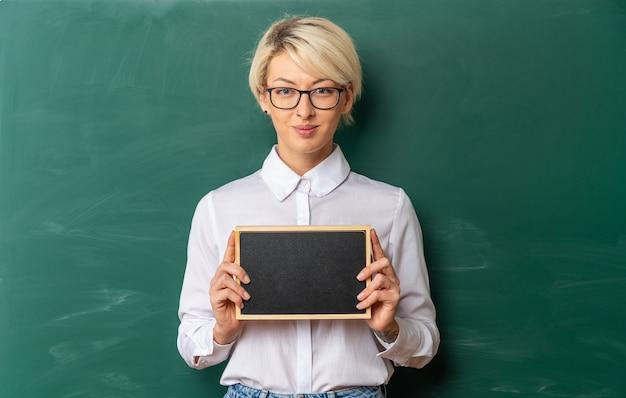Erfreute junge blonde lehrerin mit brille im klassenzimmer, die vor der tafel steht und eine mini-tafel mit kopienraum zeigt