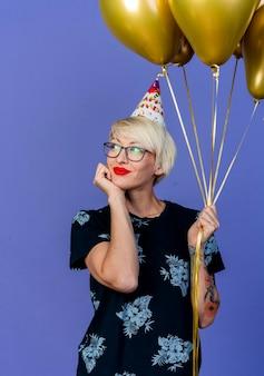 Erfreute junge blonde partyfrau, die brille und geburtstagskappe hält, die luftballons hält, die hand unter kinn setzen und seite betrachten, die lokal auf lila wand träumt