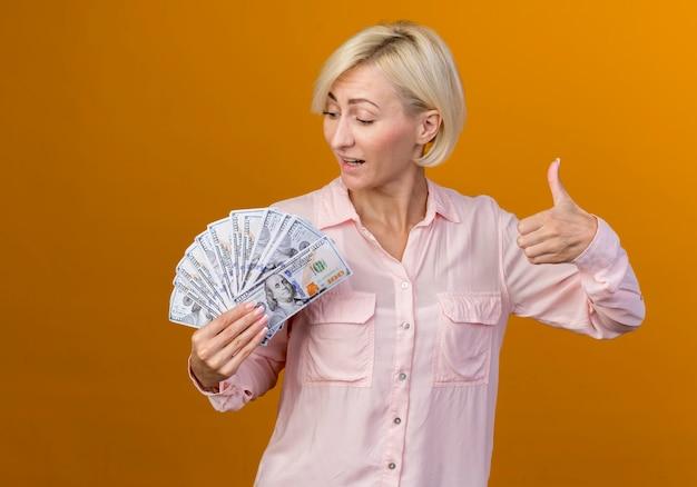 Erfreute junge blonde slawische frau, die bargeld ihren daumen oben lokalisiert auf orange hintergrund hält