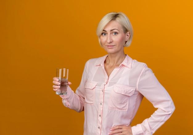 Erfreute junge blonde slawische frau, die glas wasser hält und hand auf hüfte legt