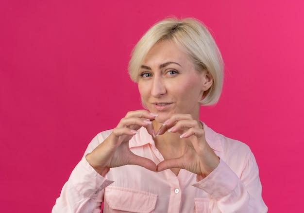 Erfreute junge blonde slawische frau, die kamera betrachtet und herzzeichen lokalisiert auf rosa hintergrund tut