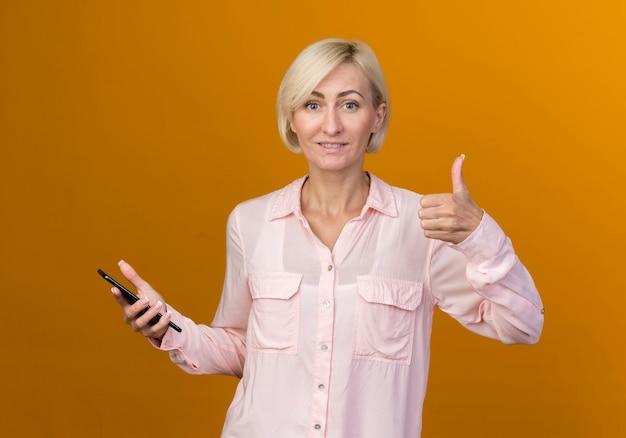 Erfreute junge blonde slawische frau, die telefon und ihren daumen oben auf orange wand lokalisiert hält