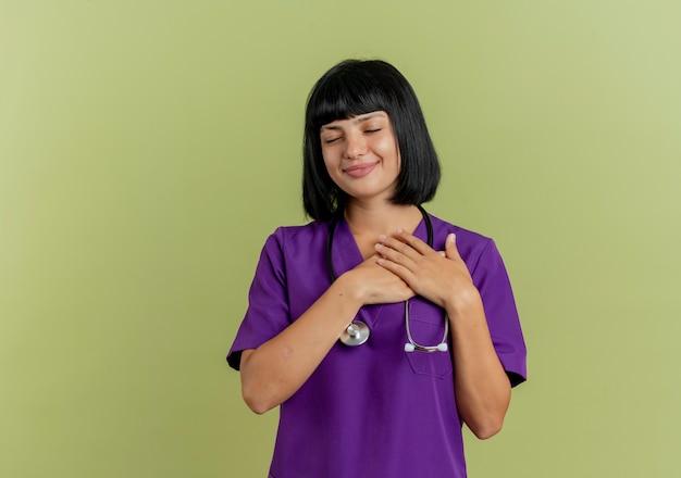 Erfreute junge brünette ärztin in uniform mit stethoskop legt hände auf brust isoliert auf olivgrünem hintergrund mit kopienraum