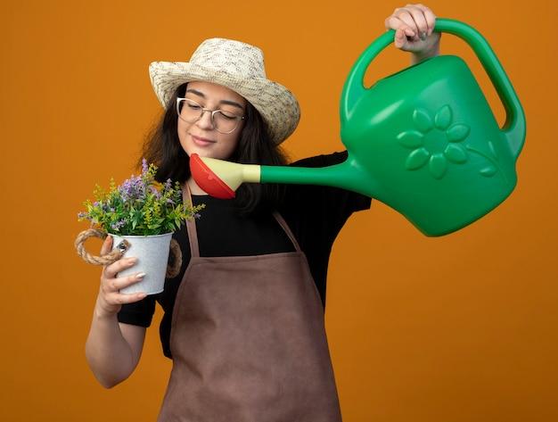 Erfreute junge brünette gärtnerin in optischen gläsern und in uniform, die gartenhut trägt, gibt vor, blumen im blumentopf mit gießkanne zu gießen isoliert auf orange wand mit kopienraum