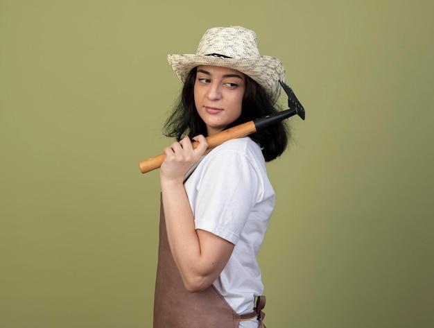 Erfreute junge brünette gärtnerin in uniform mit gartenhut steht seitlich