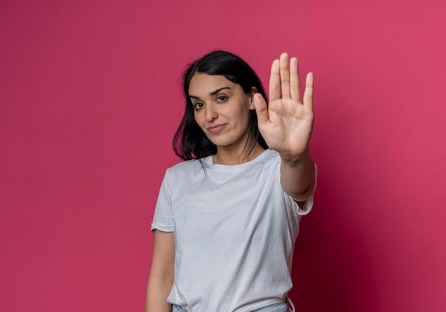 Erfreute junge brünette kaukasische mädchengesten stoppen handzeichen lokalisiert auf rosa wand