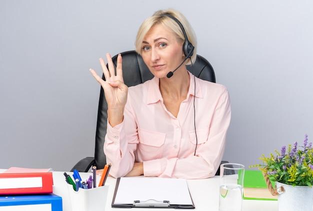 Erfreute junge callcenter-betreiberin mit headset am tisch sitzend mit bürowerkzeugen, die vier zeigen
