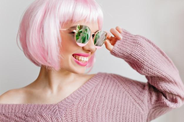 Erfreute junge dame in der perücke, die während des innenfotoshootings lächelt. nahaufnahmeporträt der lachenden stilvollen frau mit rosa haaren, die in funkelnden gläsern aufwerfen.