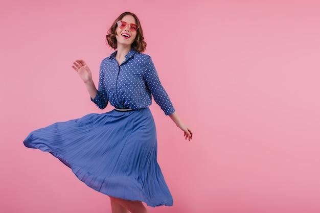 Erfreute junge dame in eleganter bluse, die mit hübschem lächeln tanzt. innenporträt des glückseligen lockigen mädchens im midirock entspannend während des fotoshootings.