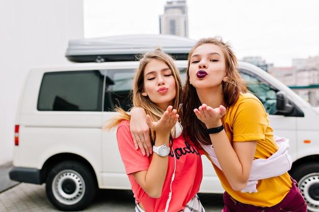Erfreute junge damen in stilvollem sommeroutfit posieren mit schönem gesichtsausdruck, bevor sie mit dem weißen auto davonfahren