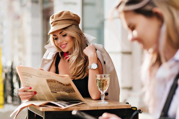 Erfreute junge frau, die lustigen artikel liest und lacht, während sie im open-air-café sitzt. fröhliches blondes mädchen, das zeitung hält und lächelt und champagner am wochenende genießt.