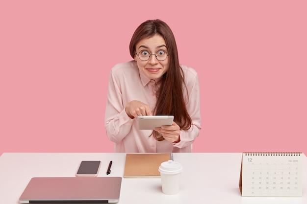 Erfreute junge frau in brille hält touchpad für online-zahlung, gekleidet in elegantes hemd, posiert allein am arbeitsplatz
