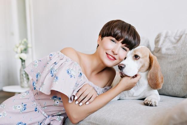 Erfreute junge frau mit weißer maniküre verträumt mit ihrem beagle-hund auf hellgrau und lächelnd