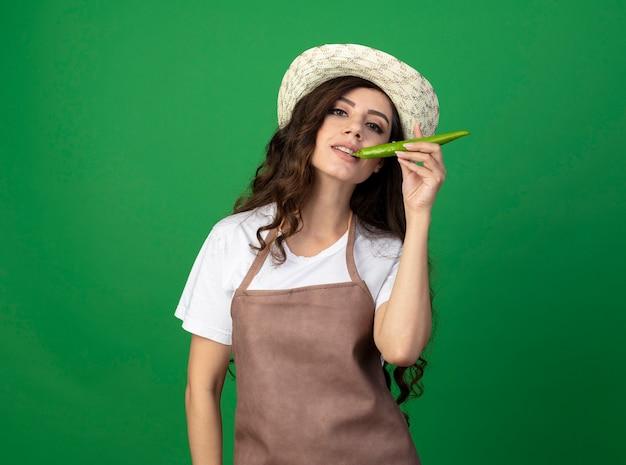 Erfreute junge gärtnerin in uniform, die gartenhut trägt, beißt heißen pfeffer lokalisiert auf grüner wand