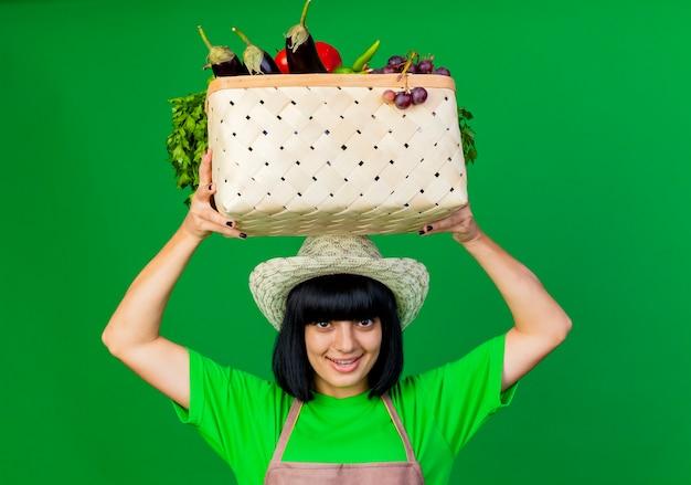 Erfreute junge gärtnerin in uniform mit gartenhut hält gemüsekorb über kopf