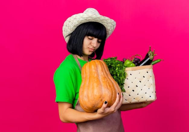 Erfreute junge gärtnerin in uniform mit gartenhut hält gemüsekorb und schaut auf kürbis