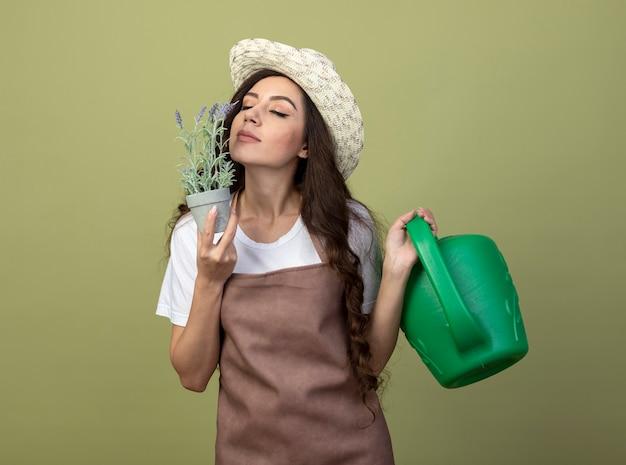 Erfreute junge gärtnerin in uniform mit gartenhut hält gießkanne und schnüffelt blumen im blumentopf isoliert auf olivgrüner wand