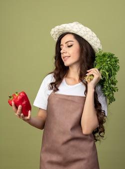 Erfreute junge gärtnerin in uniform mit gartenhut hält koriander und betrachtet roten pfeffer isoliert auf olivgrüner wand mit kopienraum