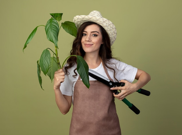 Erfreute junge gärtnerin in uniform mit gartenhut hält pflanzen- und gartenschere isoliert auf olivgrüner wand
