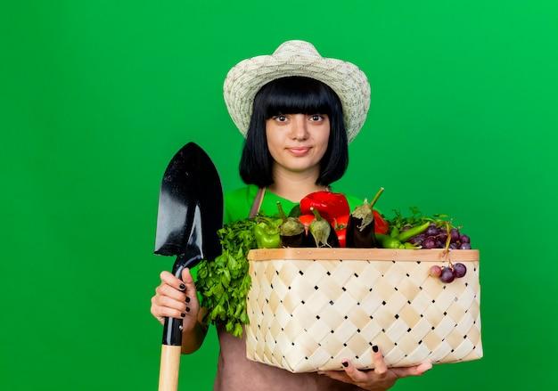 Erfreute junge gärtnerin in uniform mit gartenhut hält spaten und gemüsekorb