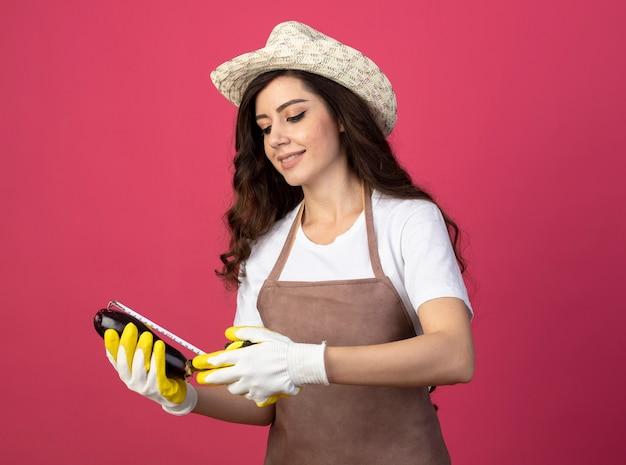 Erfreute junge gärtnerin in uniform mit gartenhut und handschuhen, die auberginen mit maßband messen, isoliert auf rosa wand mit kopienraum