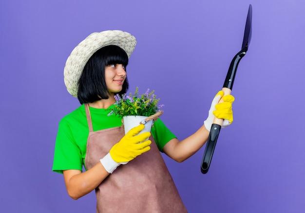 Erfreute junge gärtnerin in uniform mit gartenhut und handschuhen hält blumentopf und schaut auf spaten