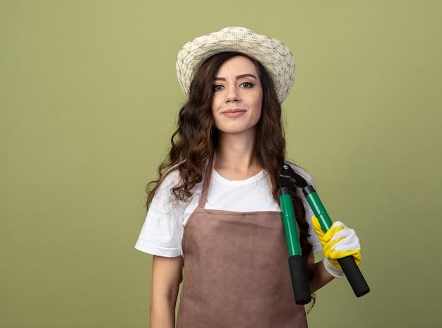 Erfreute junge gärtnerin in uniform mit gartenhut und handschuhen hält gartenschere auf schulter isoliert auf olivgrüner wand