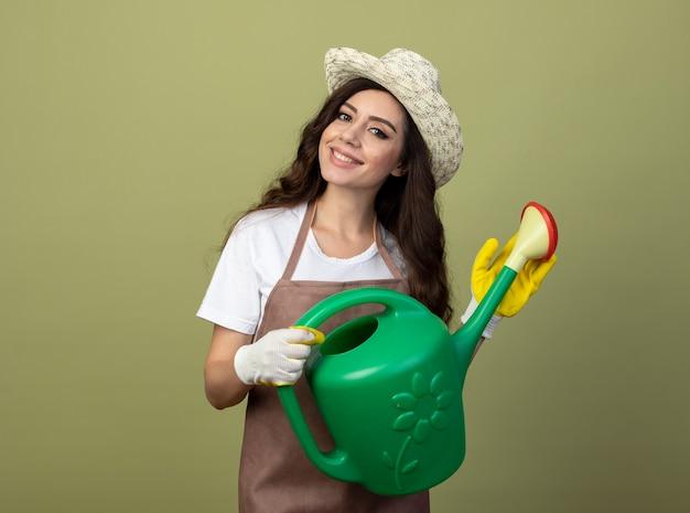 Erfreute junge gärtnerin in uniform mit gartenhut und handschuhen hält gießkanne isoliert auf olivgrüner wand
