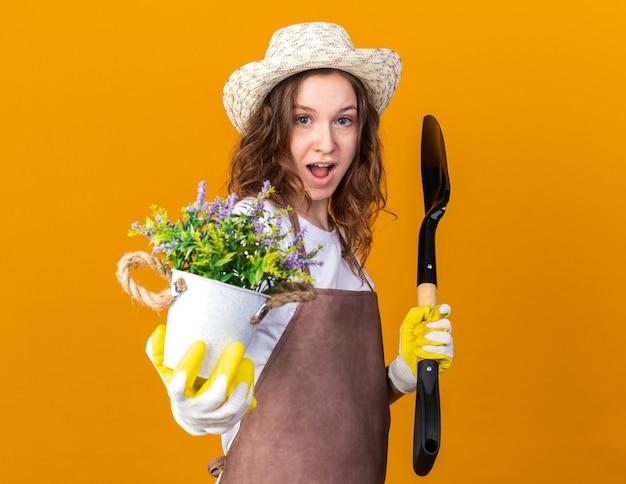 Erfreute junge gärtnerin mit gartenhut mit handschuhen, die blume im blumentopf mit spaten halten