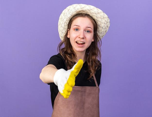 Erfreute junge gärtnerin mit gartenhut mit handschuhen, die die hand isoliert auf blauer wand halten
