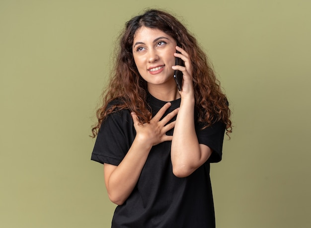 Erfreute junge hübsche frau, die am telefon spricht und aufschaut, danke geste isoliert auf olivgrüner wand mit kopierraum