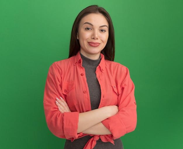 Erfreute junge hübsche frau, die mit geschlossener haltung steht und kamera lokalisiert auf grünem hintergrund mit kopienraum betrachtet