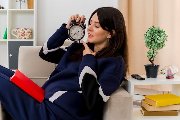 Erfreute junge hübsche kaukasische frau, die auf sessel in entworfenem wohnzimmer sitzt, das betrachtet und auf wecker mit geschlossenem buch auf beinen zeigt