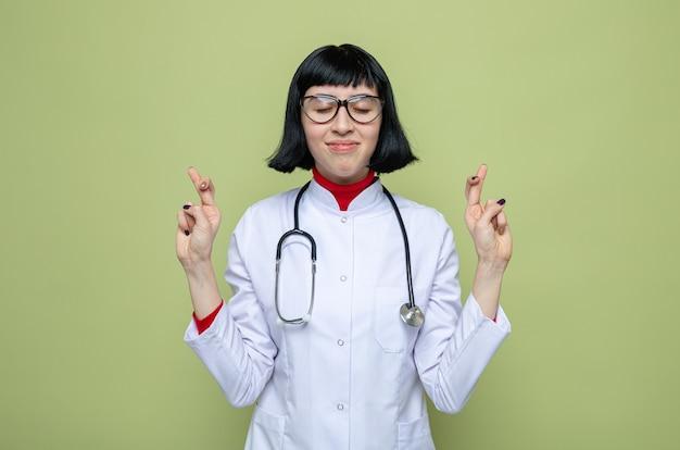 Erfreute junge hübsche kaukasische frau mit brille in arztuniform mit stethoskop, die mit geschlossenen augen steht und die finger kreuzt