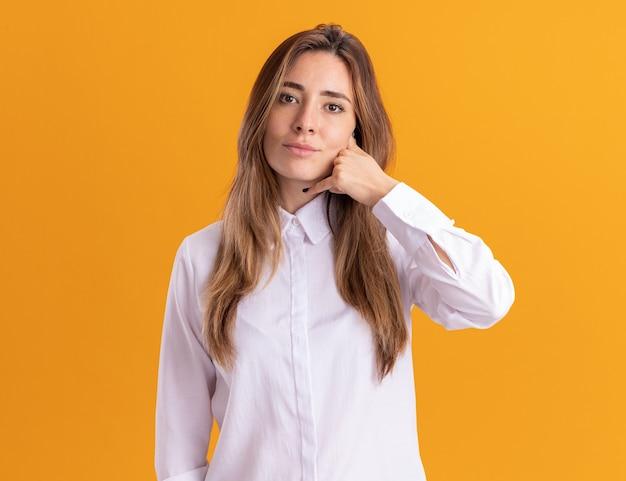 Erfreute junge hübsche kaukasische mädchengesten nennen mich zeichen auf orange