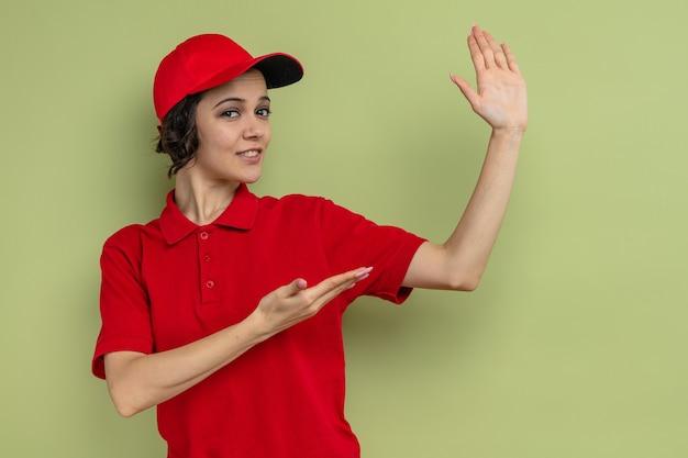 Erfreute junge hübsche lieferfrau, die auf ihre hand zeigt