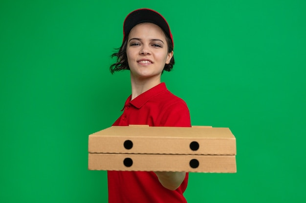 Erfreute junge hübsche lieferfrau, die pizzakartons heraushält