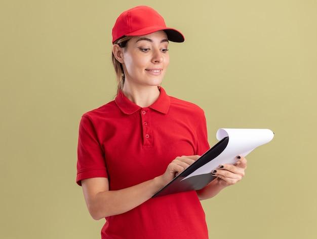 Erfreute junge hübsche lieferfrau in uniform hält und schaut auf zwischenablage isoliert auf olivgrüner wand