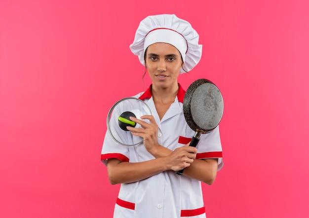 Erfreute junge köchin, die kochuniform trägt, die bratpfanne mit deckel auf isolierter rosa wand mit kopienraum hält und kreuzt