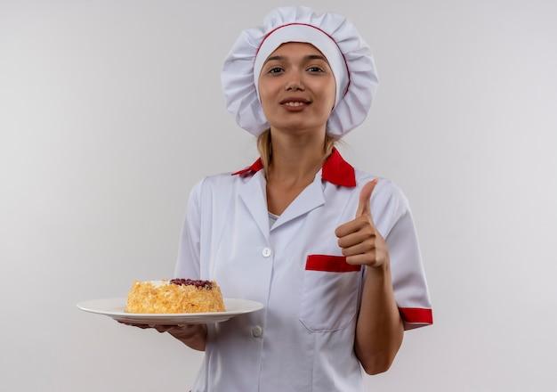 Erfreute junge köchin, die kochuniform trägt, die kuchen auf platte ihren daumen oben auf isolierter weißer wand mit kopienraum hält