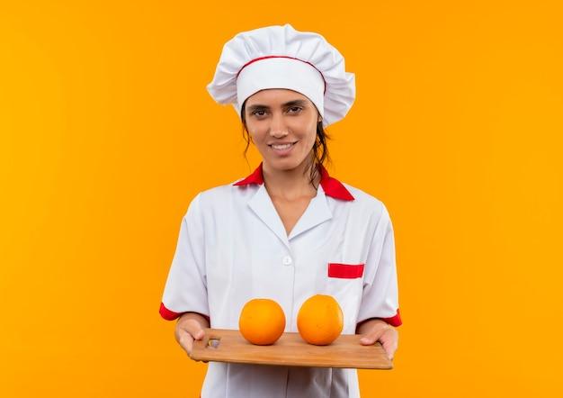 Erfreute junge köchin, die kochuniform trägt, die orange auf schneidebrett auf isolierter gelber wand mit kopienraum hält