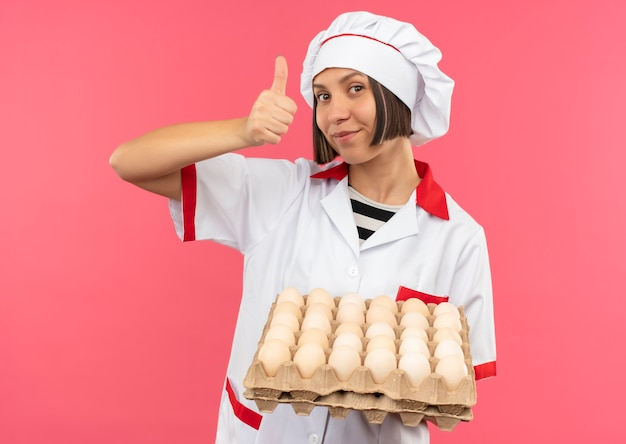 Erfreute junge köchin in der kochuniform, die karton der eier hält und daumen oben auf rosa hintergrund zeigt