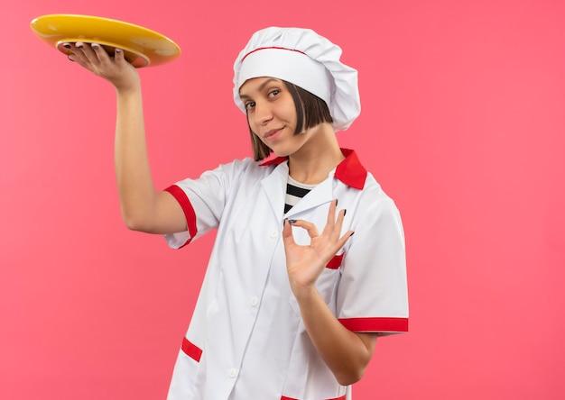 Erfreute junge köchin in der kochuniform, die leere platte hält und ok zeichen lokalisiert auf rosa wand tut