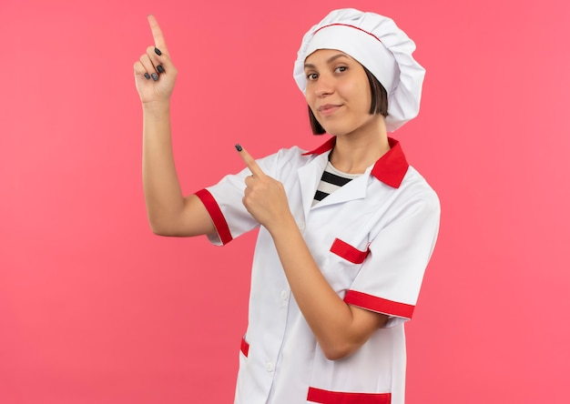 Erfreute junge köchin in der kochuniform, die lokal auf rosa wand zeigt