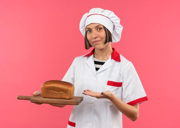 Erfreute junge köchin in der kochuniform, die mit der hand auf schneidebrett mit brot auf lokalisiertem rosa hintergrund hält und zeigt