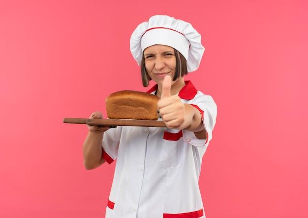 Erfreute junge köchin in der kochuniform, die schneidebrett mit brot darauf hält und daumen oben auf rosa hintergrund mit kopienraum zeigt